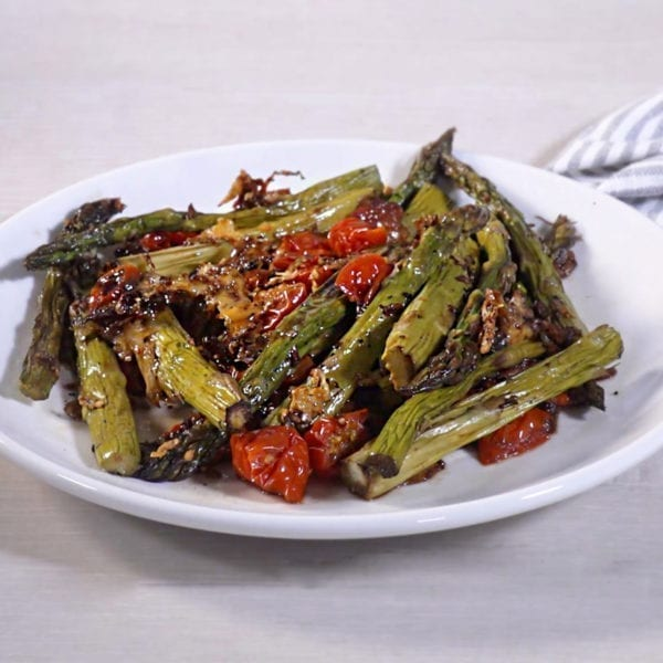 Parmesan Roasted Asparagus and Tomatoes on a white plate.