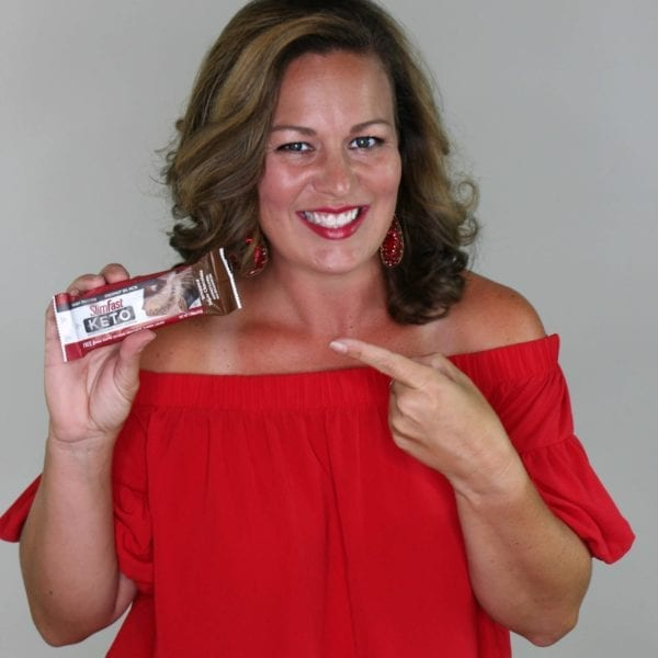 Amanda in a red top holding a chocolate Keto meal bar and pointing to it.